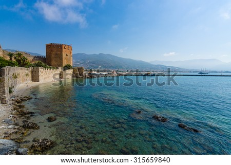 Red Tower (Kizil Kule) and the ruins of the fortress wall near the shore. The Mediterranean coast. Alanya. Turkey - stock photo