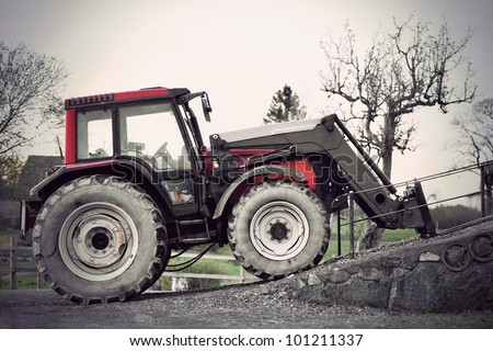 Red tractor at farm in early spring