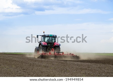 Red tractor driven by farmer cultivating land at spring - stock photo