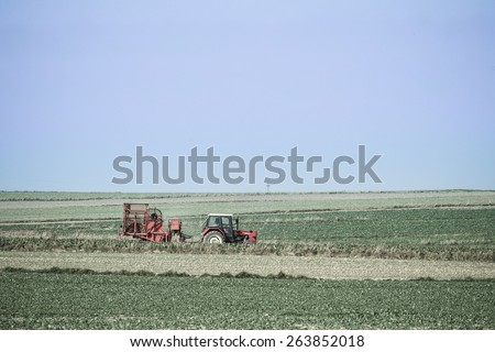 Red tractor in a spring field Tinted photo of a spring field work - stock photo