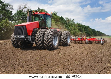 red tractor in the field; mechanism - stock photo