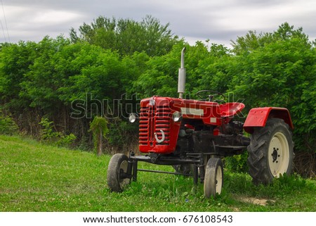 Red tractor in the field on a cloudy day