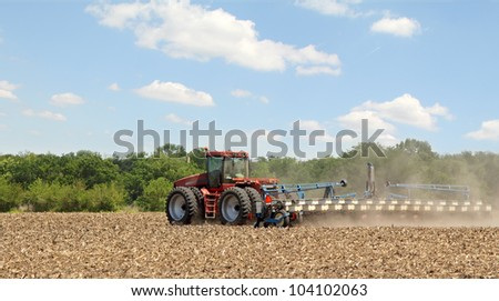 Red tractor planting crop in farm field