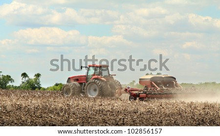Red tractor pulling a sprayer applying chemicals to farm field