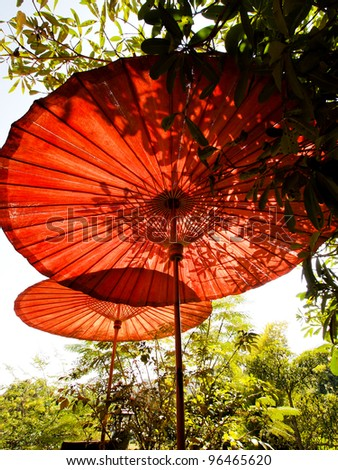 Red traditional bamboo umbrellas with leaf shadow under the sun - stock photo