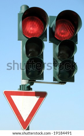 Red traffic light and give place sign.