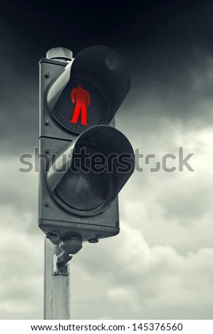 Red traffic light for pedestrians against gray cloudy sky. Stop obligation.