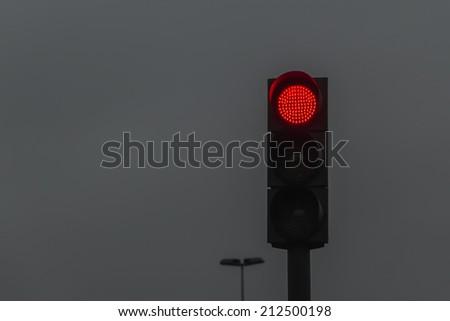 Red traffic light on dark sky  - stock photo