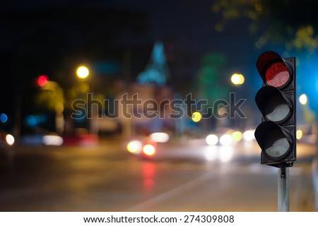 Red traffic light on the road during the night. light sign for car stop and speed reduction. Dangerous,warning signal,semaphore driving. - stock photo