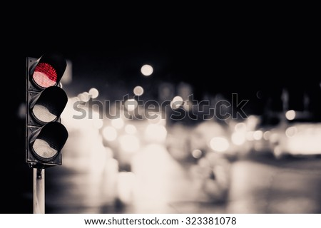 Red traffic light on the road during the night. light sign for car stop and speed reduction. - stock photo