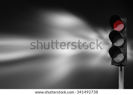 Red traffic light on the road during the night. light sign for car stop and speed reduction. Dangerous,warning signal,semaphore driving. Abstract blurred light background. - stock photo