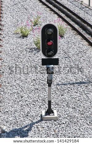 red traffic light on the train tracks - stock photo