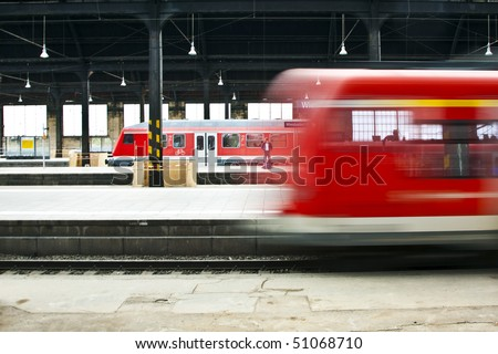 red train in motion in the station - stock photo