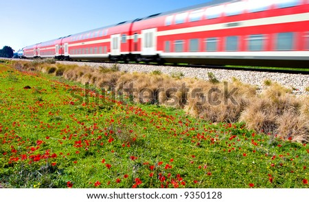 Red train moving fast in a field