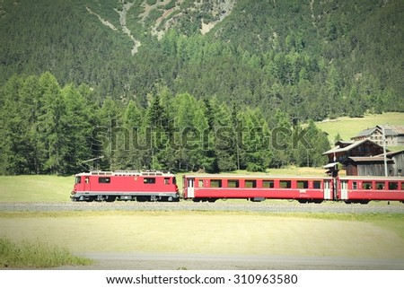 Red train on a scenic route in Grisons (Graubunden) Canton of Switzerland. Alpine railway. Cross processing color style - retro filtered tone. - stock photo