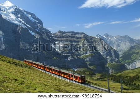 red train on the background of snowy peaks in the Swiss Alps - stock photo
