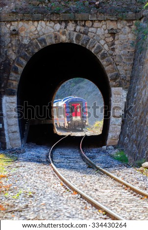 Red train out of train tunnel - stock photo