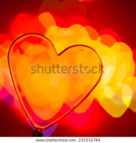 Red transparent plastic heart with blured lights in background, very shallow DOF - stock photo