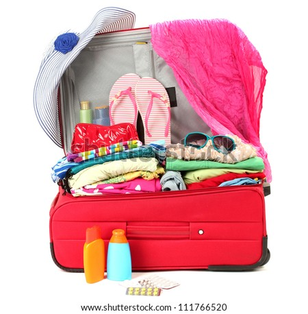 Red travel suitcase with personal belongings isolated on white - stock photo