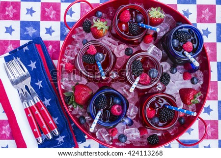 Red tray filled with ice holding mason jar mugs filled with berry iced tea and straws on patriot decorated picnic table