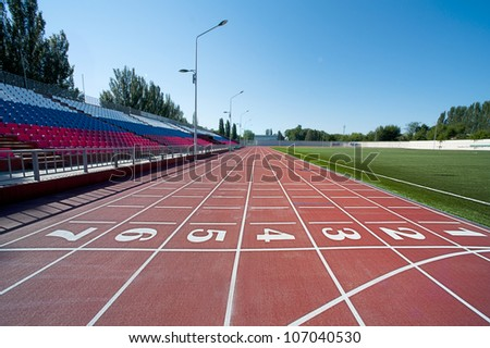 Red treadmill at the stadium with the numbering from one to seven - stock photo