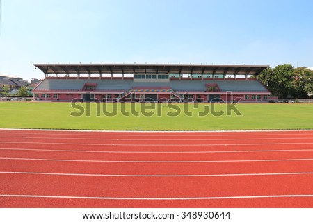 Red treadmill, track running at the stadium with green grass on blue sky - stock photo