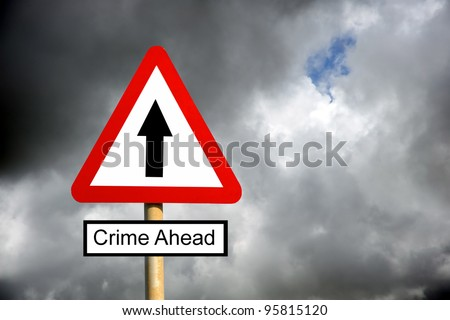 Red triangle Crime Ahead warning sign against a cloudy stormy sky