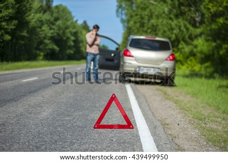Red triangle warning sign closeup, man calling to a car assistance after breakdown. Selective focus