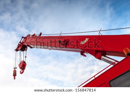 Red truck crane boom with hooks and scale weight above blue sky - stock photo