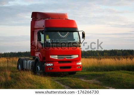 Red truck on autumn field - stock photo