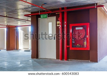 Red Tubepipe System Under Ceiling Parking Stock Photo
