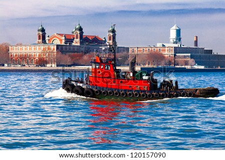 Red tugboat passing in front of historic Ellis Island in the New York City harbor. - stock photo