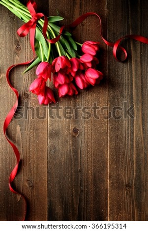 Red tulip bouquet with red ribbon on the wooden background - stock photo