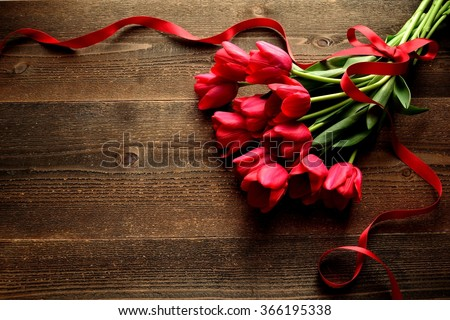 Red tulip bouquet with red ribbon on the wooden background