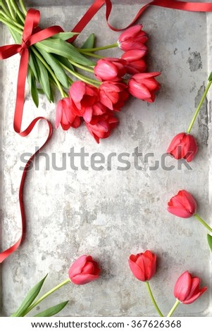 Red tulip bouquet with ribbon on the silver background.Image of spring flower on anniversary and Valentines day - stock photo