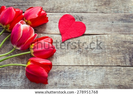 Red tulips and red heart on a wooden background - stock photo