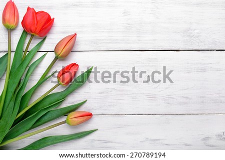 Red tulips flowers bouquet on old white wooden background. Top view with copy space - stock photo