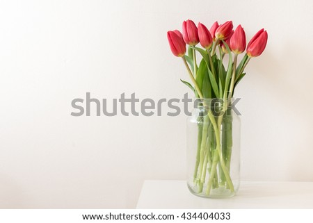Red tulips in tall glass jar on edge of white table against white wall