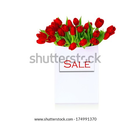 Red tulips in white shopping bag with text Sale. Greeting card, advertising, holiday background. Isolated, over white background, with copy space - stock photo