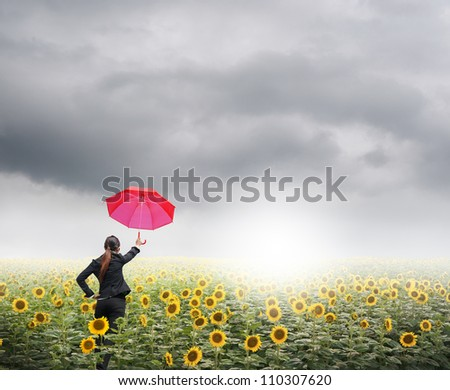 Red umbrella Business woman standing in rainclouds over sunflowers field - stock photo