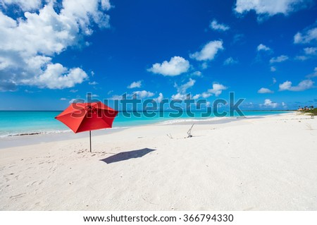 Red umbrella on Idyllic tropical beach with white sand, turquoise ocean water and blue sky at deserted island in Caribbean - stock photo