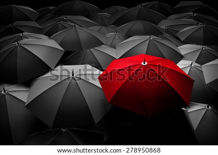 Red umbrella stand out from the crowd of many black and white umbrellas. Business, leader concept, being different concepts - stock photo