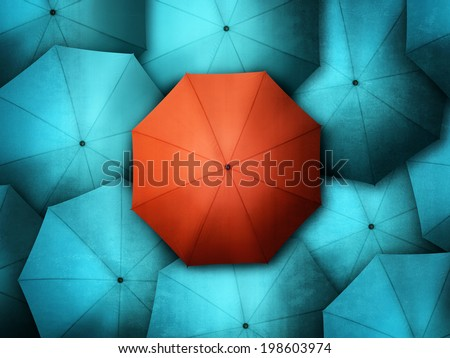 Red umbrella standing out from the crowd of blue brollys - stock photo