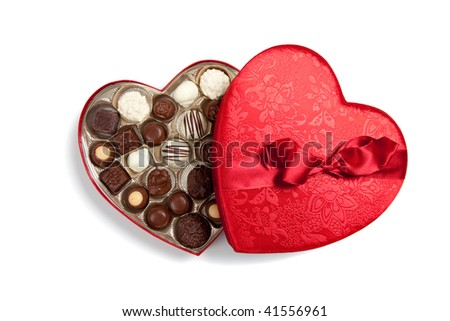 Red valentine heart filled with chocolates on a white background - stock photo