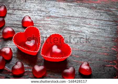 Red Valentines Day heart shaped candy border on dark  texture wooden background