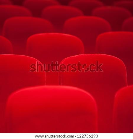 Red velvet armchairs in the empty auditorium - stock photo