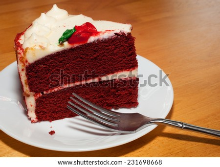 Red velvet cake on a white plate with a fork ready - stock photo