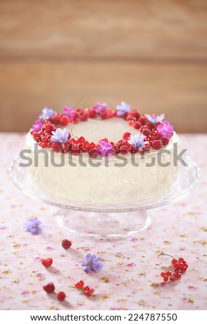 Red Velvet Cake with Cream Cheese Frosting, decorated with fresh berries and flowers. - stock photo