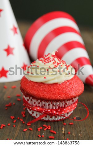Red velvet cupcake and birthday hats in background