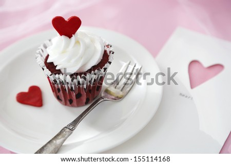 Red velvet cupcake with vanilla icing decorated with a red heart made of chocolate - stock photo